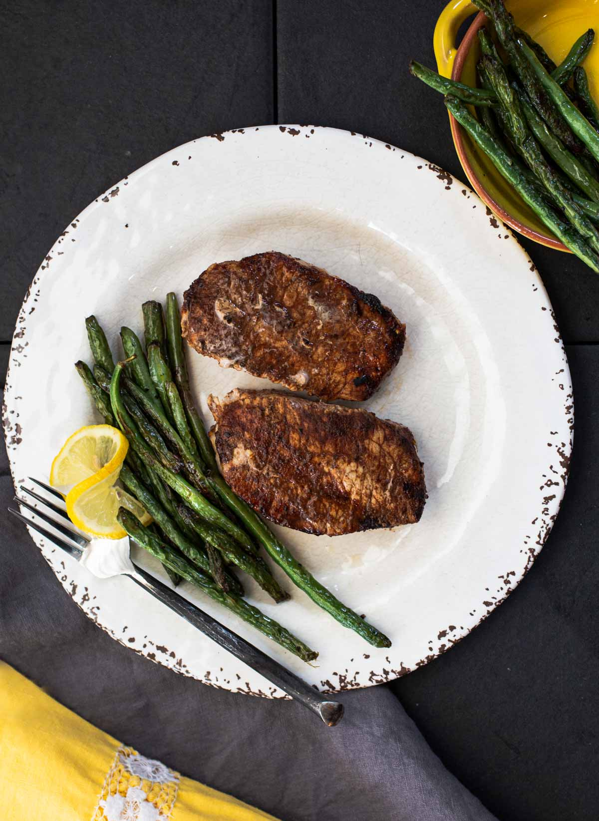 Cocoa chile powder rubbed grilled pork chops with sauteed green beans on a rustic white plate with a wedge of lemon