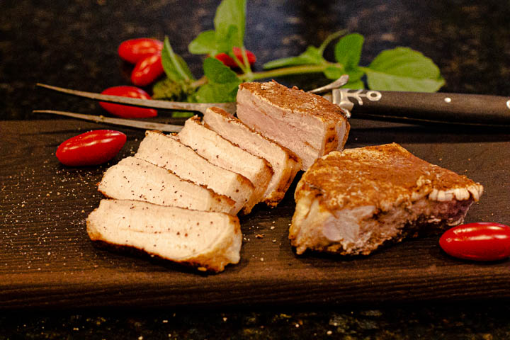 Sliced grilled butterfly porkchops on a dark wood cutting board with an antique meat fork.
