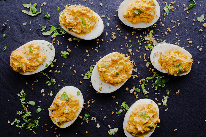 Deviled eggs on a black plate seasoned with chimayo chle powder and topped with spicy panko bread crumbs and cilantro.