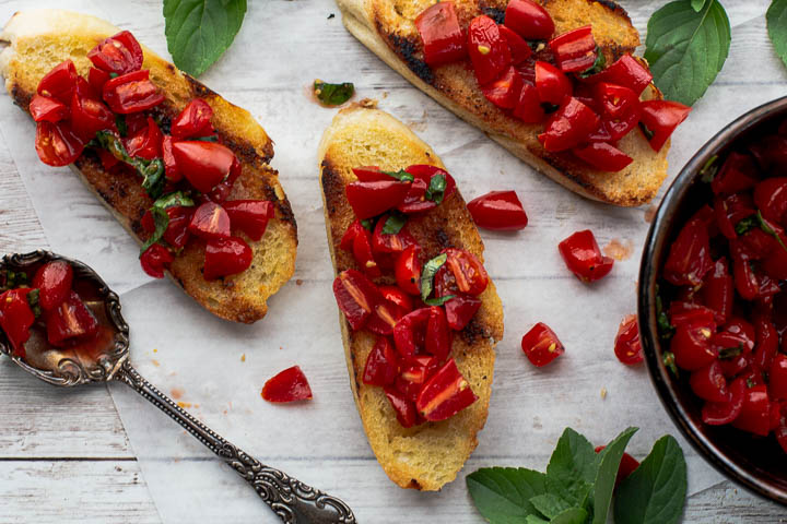 Sliced and toasted baguette topped with fresh chopped tomatoes and sprinkled with fresh slivered basil.