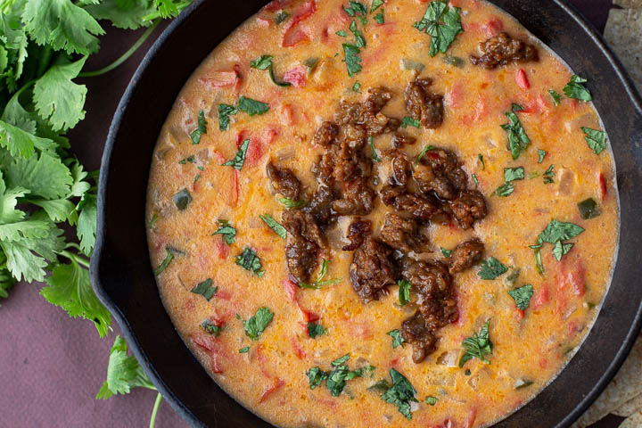 Queso fundido served in a cast iron skillet topped with cooked chorizo