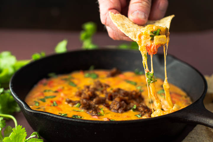 A tortilla chip dipped in queso fundido with tequila.