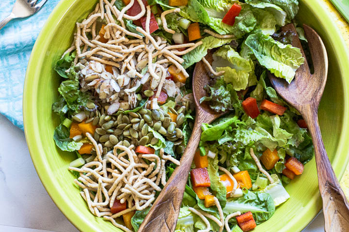 Asian lettuce salad with chow mein noodles, pepita seeds, bell pepper, and green onions.