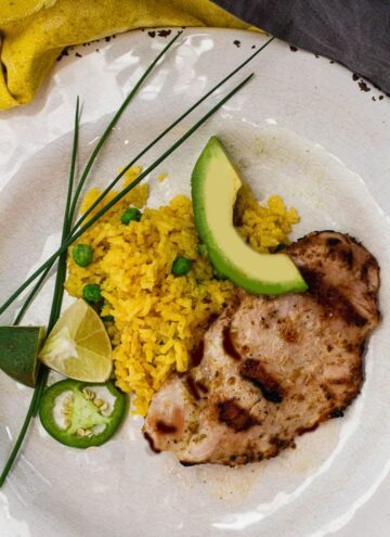 Grilled chicken cutlets seasoned with ginger and lime and served with yellow rice