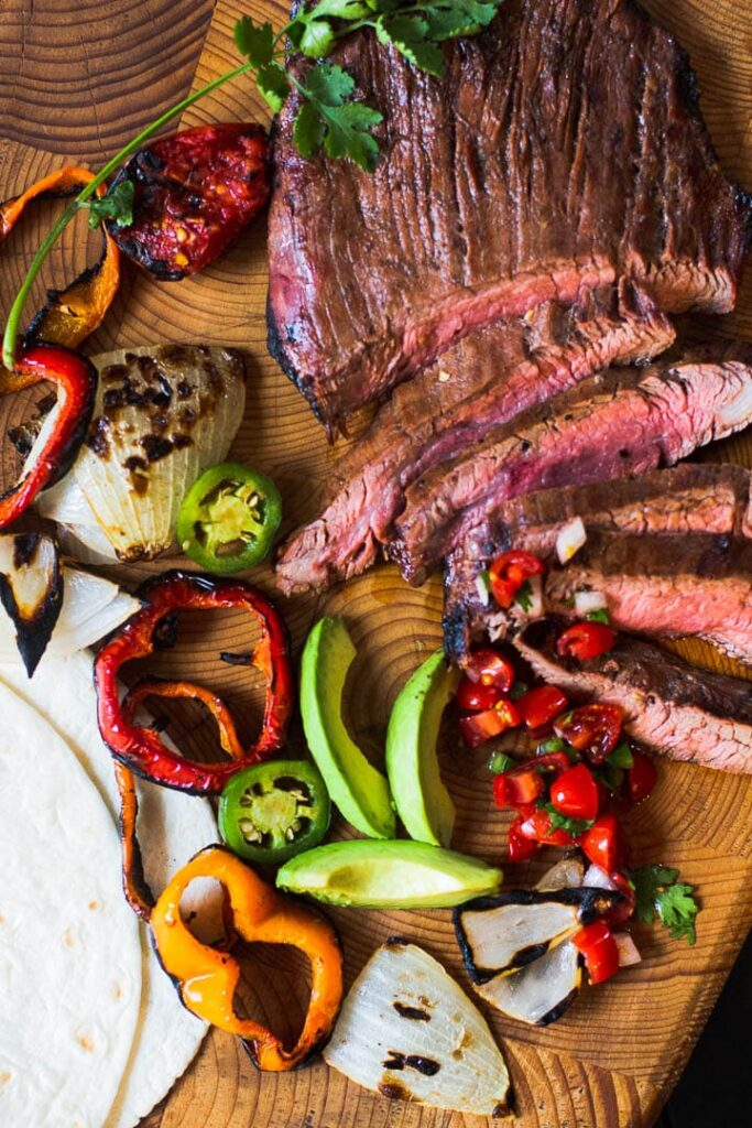 Flank Steak Fajitas served with grilled vegetables and slices of avocado