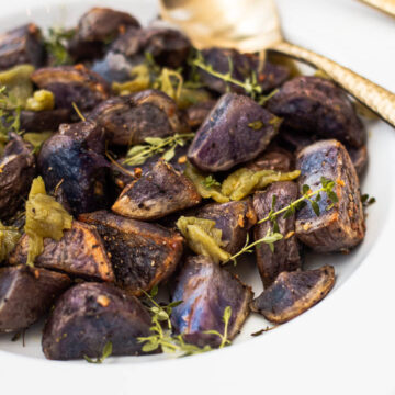 Purple roasted potatoes with garlic, thyme and green chile peppers