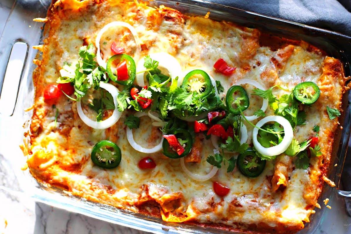 Creamy chicken enchiladas casserole baked in a pyrex baking dish.