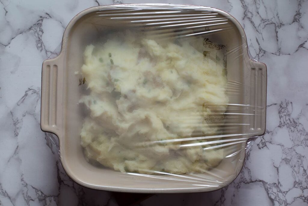 Mashed potato casserole covered with plastic wrap for storage