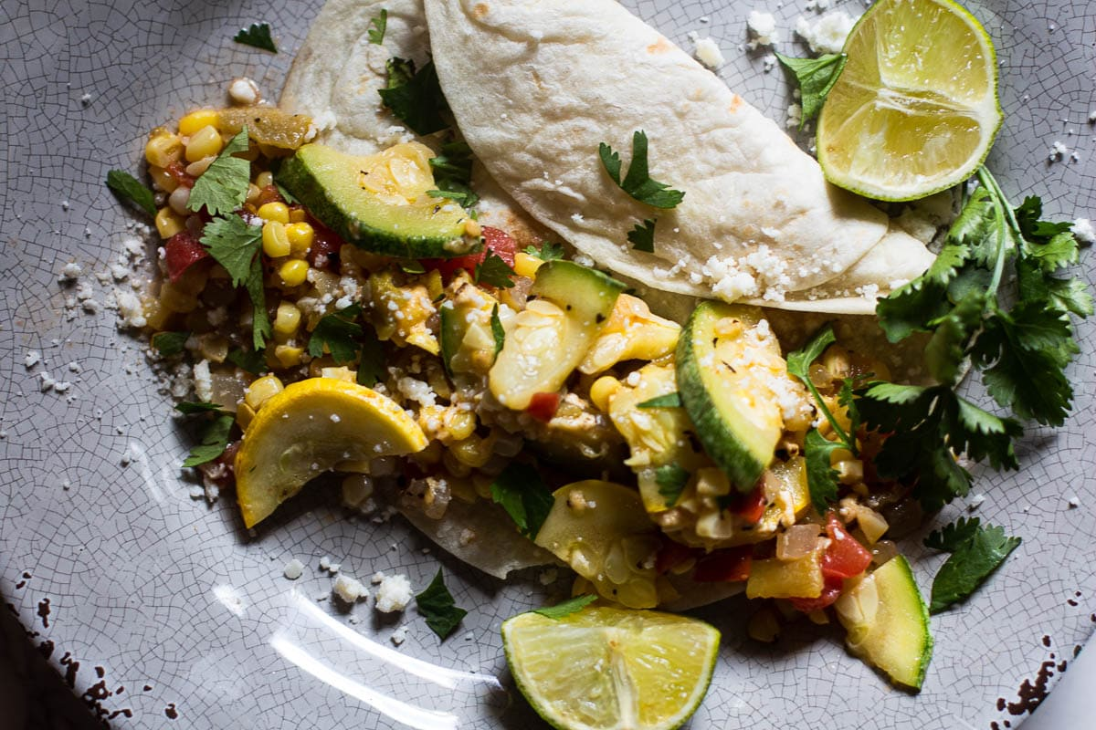 Calabacitas con queso served with lime wedges and a flour tortilla