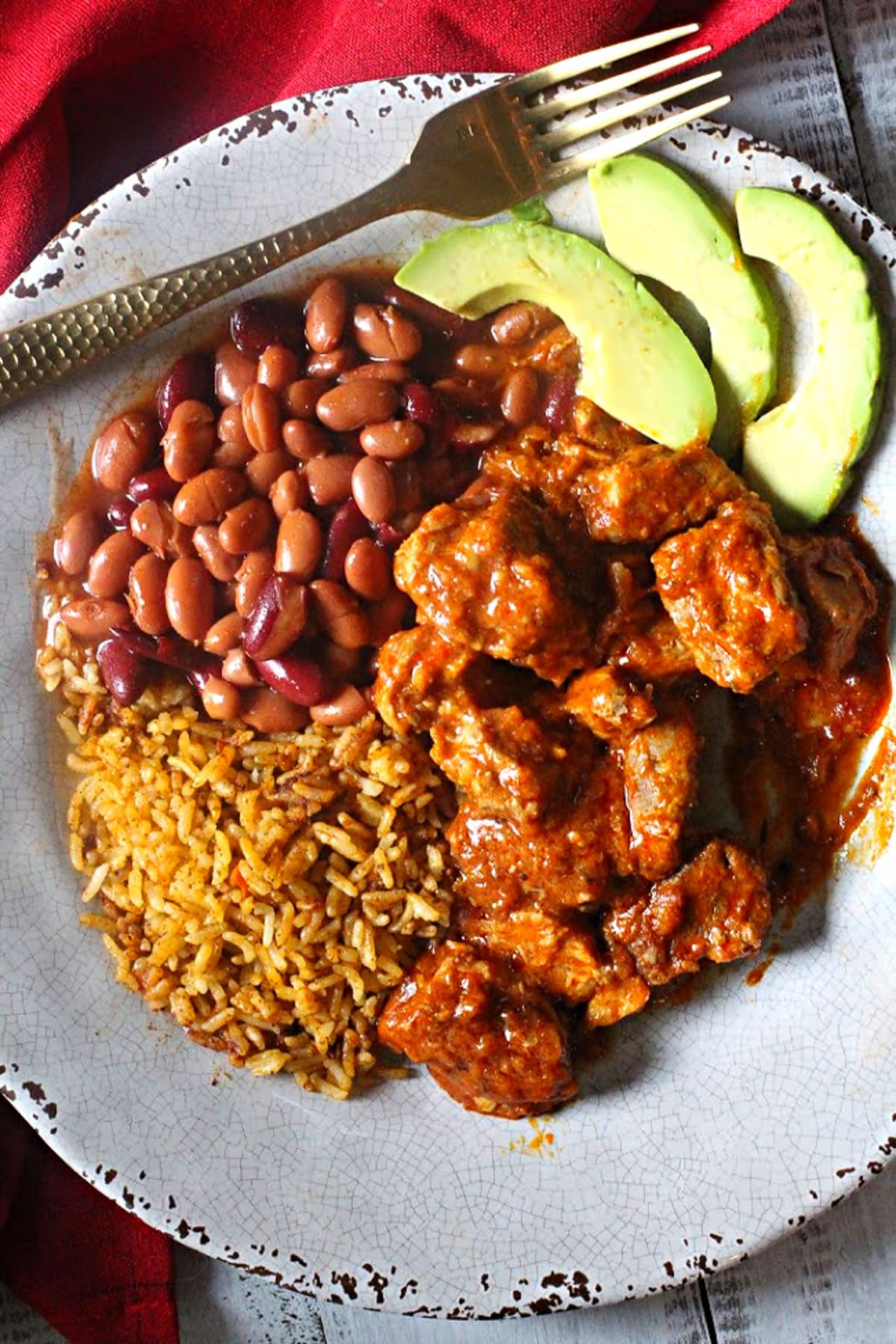 Pork braised in red chile sauce served with spanish rice, beans and slices of avocado.