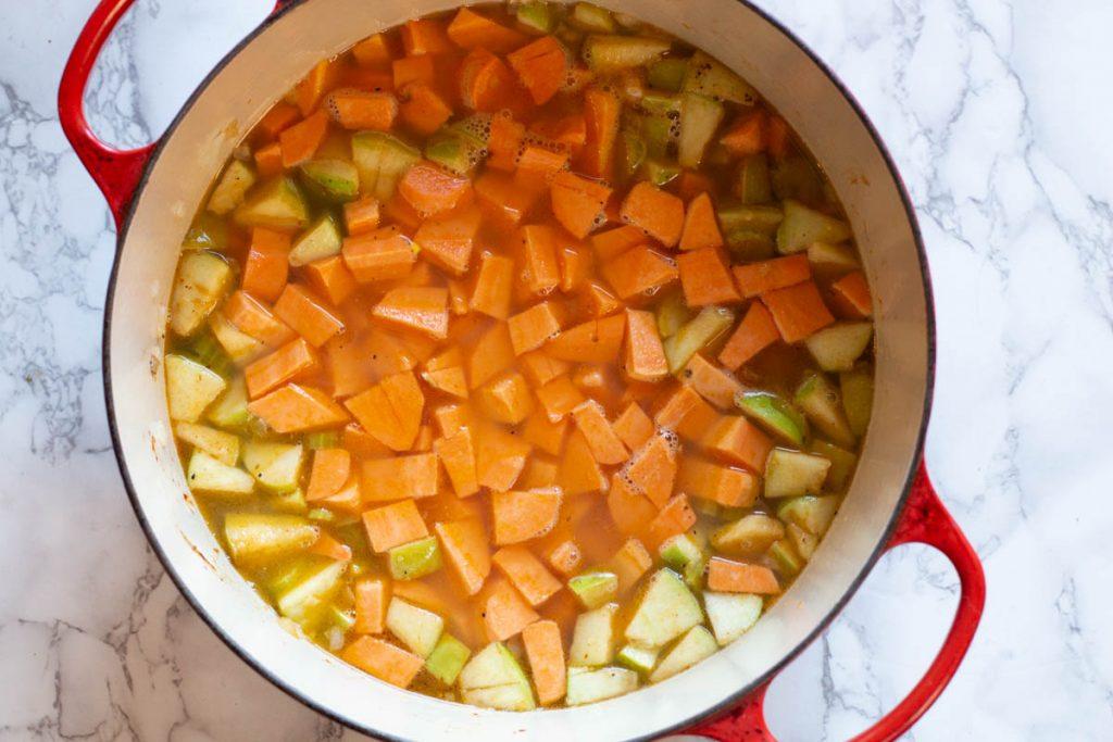 Adding sweet potatoes to broth to make sweet potato soup