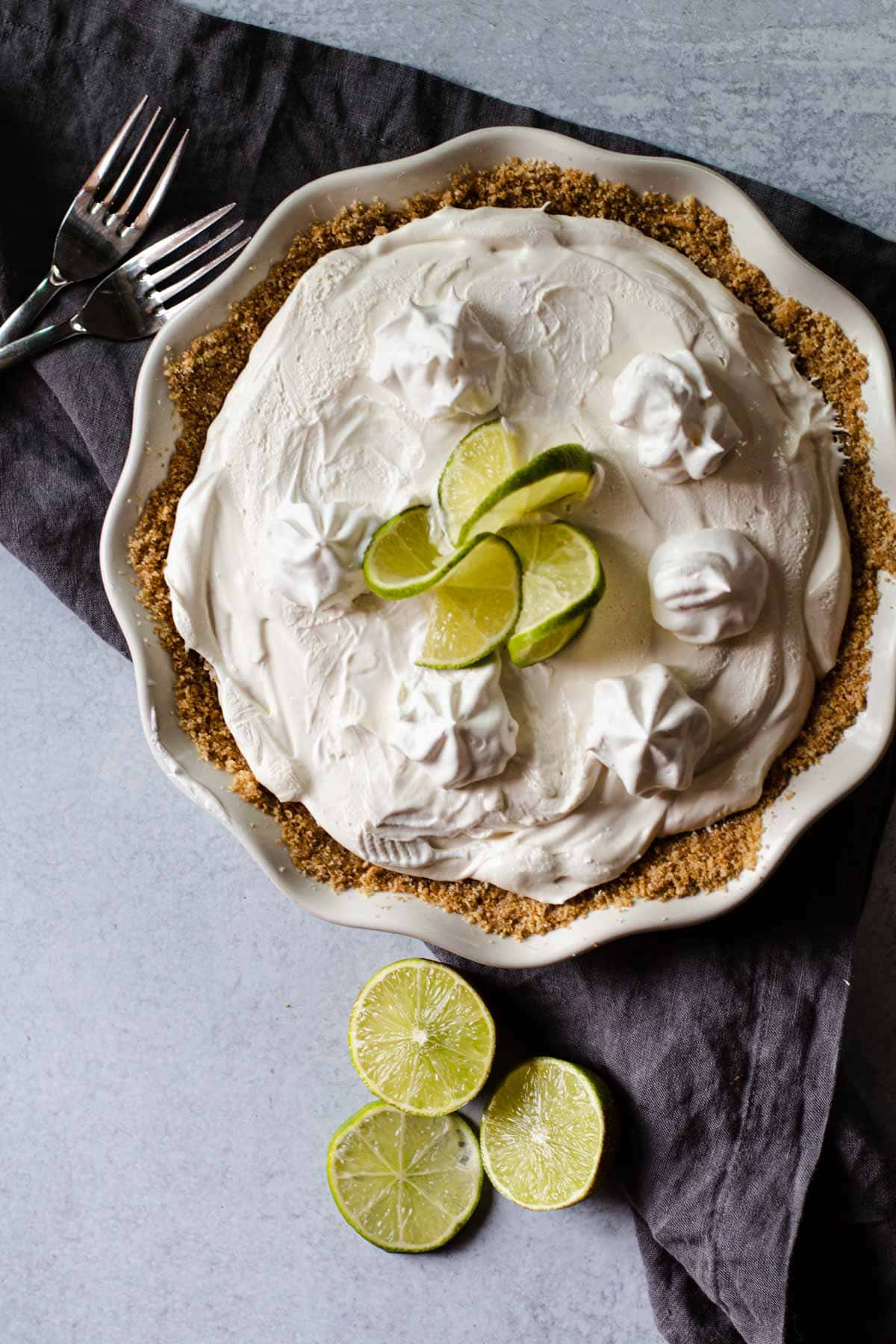 No bake key lime pie garnished with whipped cream and limes