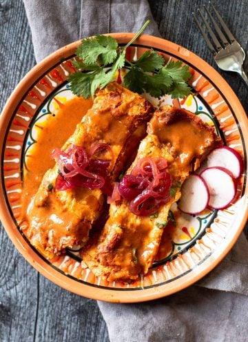 2 Pork pibel enchiladas on a festive mexican plate