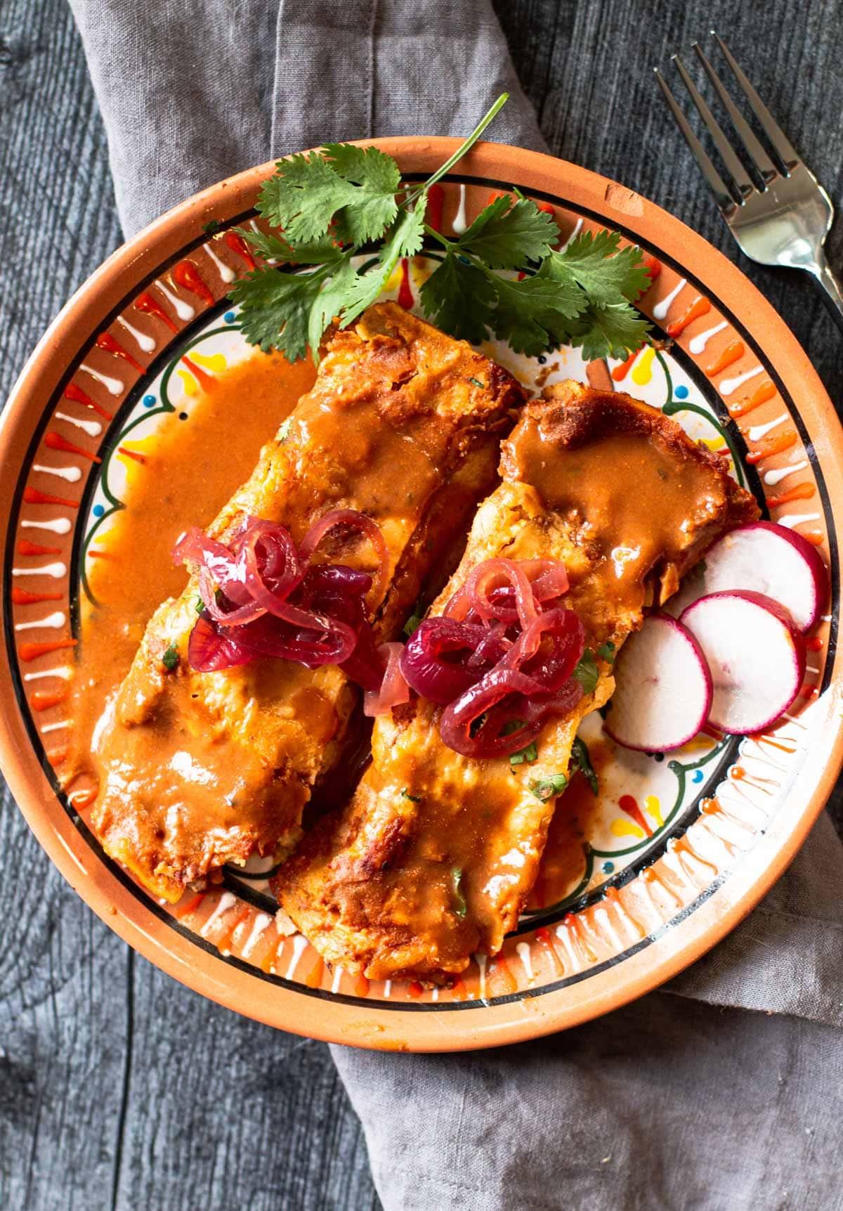 Pork Cochinita Pibel Enchiladas garnished with sliced radish and cilantro
