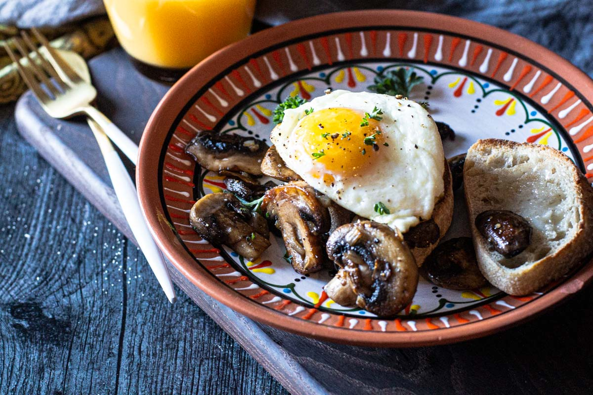 Sherried mushrooms with a sunny side up egg breakfast on rustic Italian bread