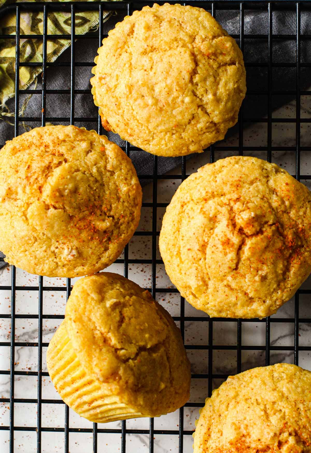 Cornbread muffins cooling on a black wire rack.