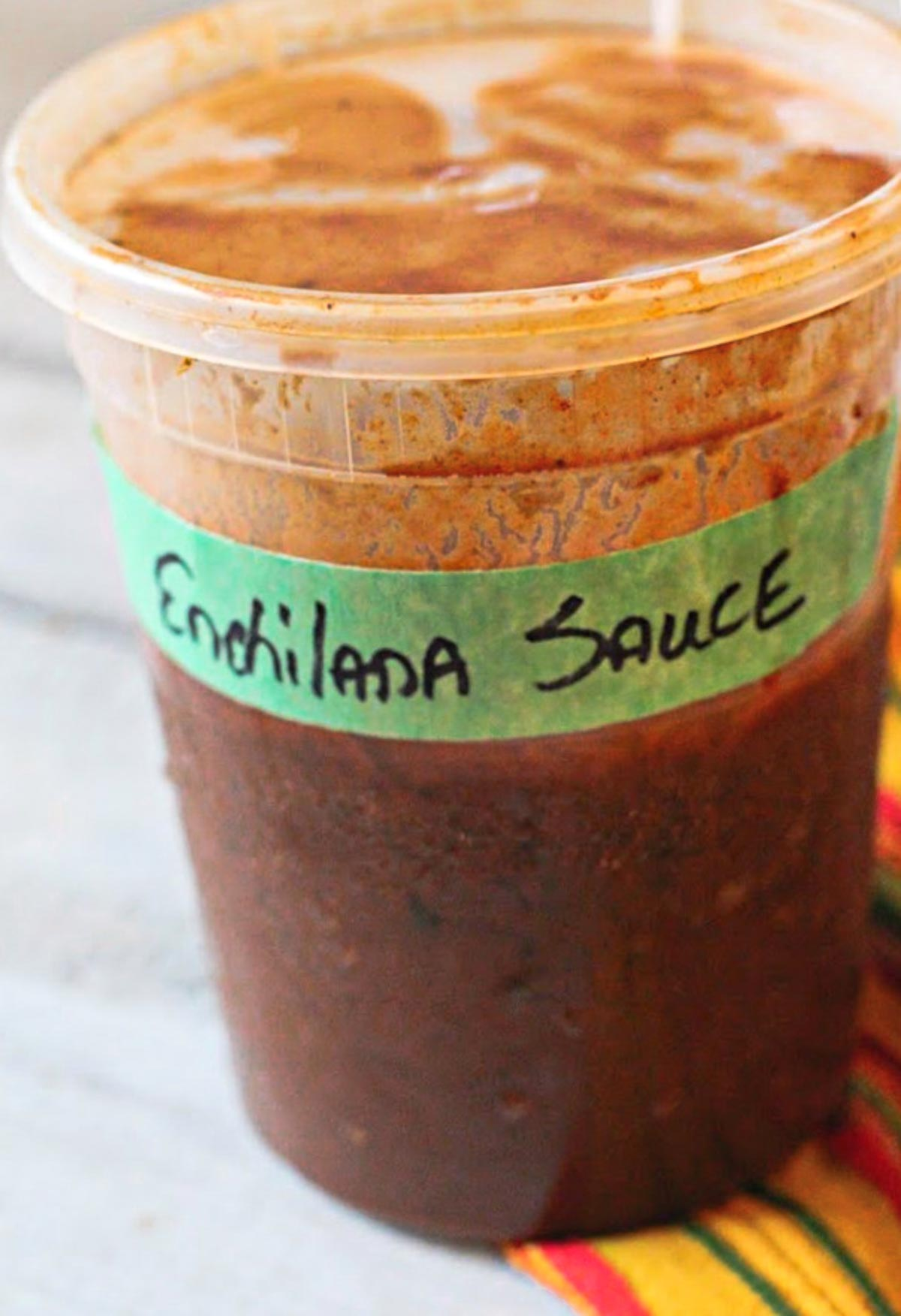 Homemade enchilada sauce stored in a deli container