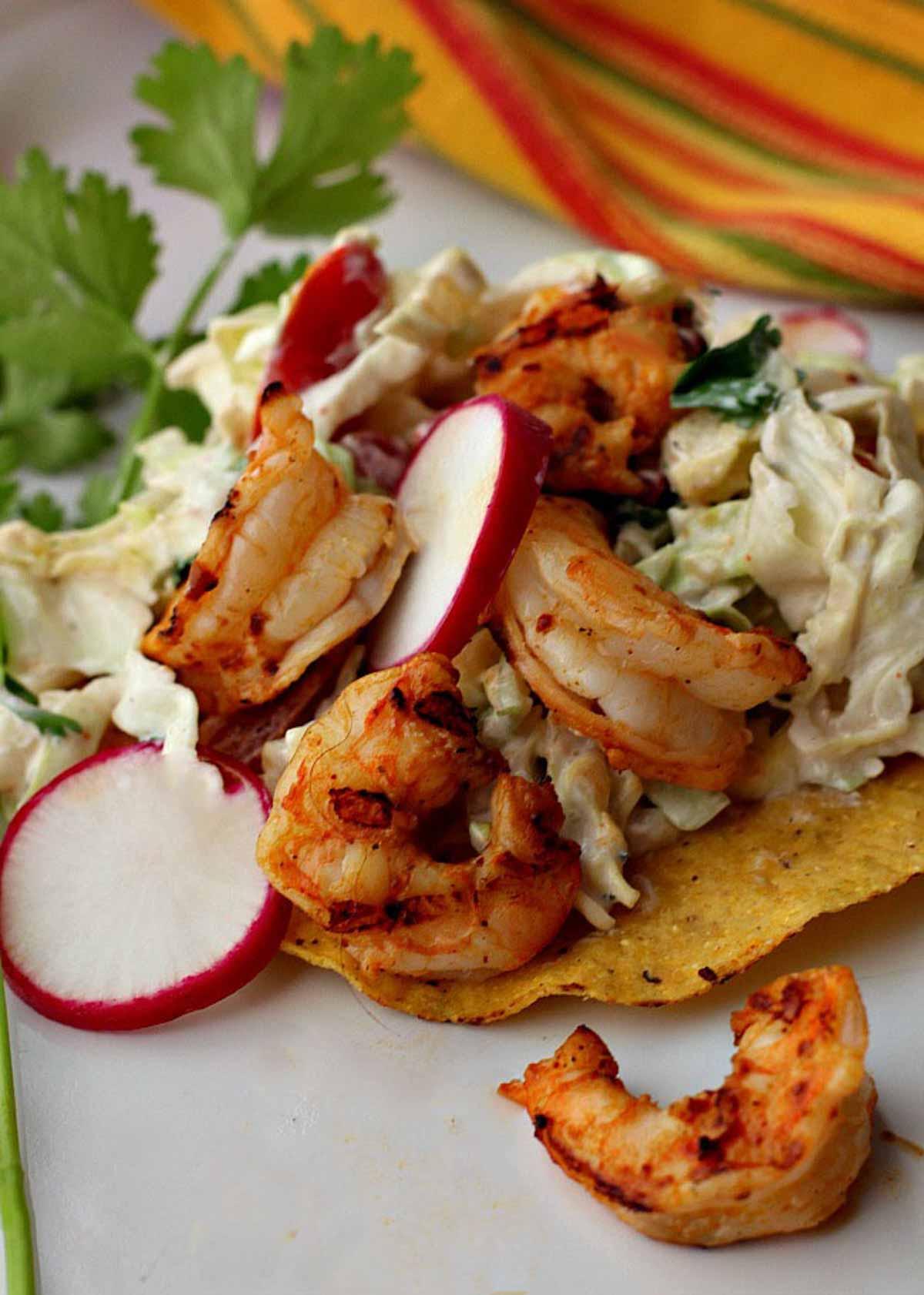 grilled shrimp tostadas with cabbage slaw on a crisp corn tortilla