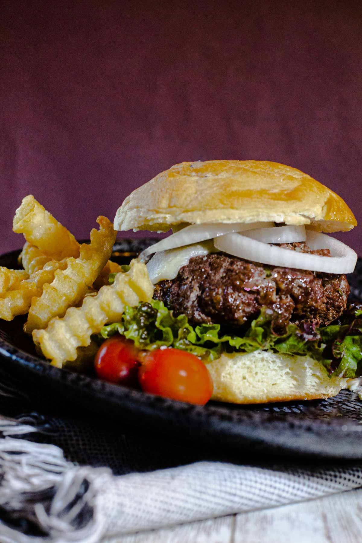Blue cheese burger recipe topped with rings of onion and tomato with crinkle fries.