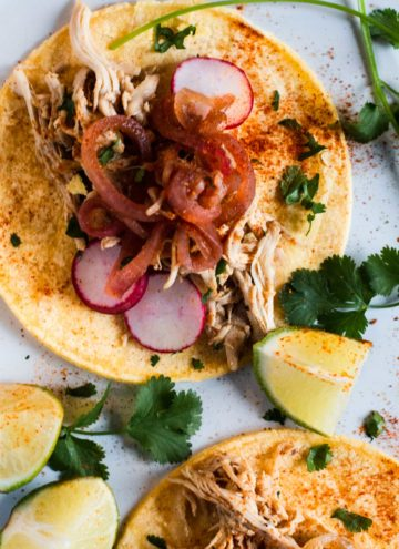 Chicken barbacoa served with corn tortillas and pickled onions.