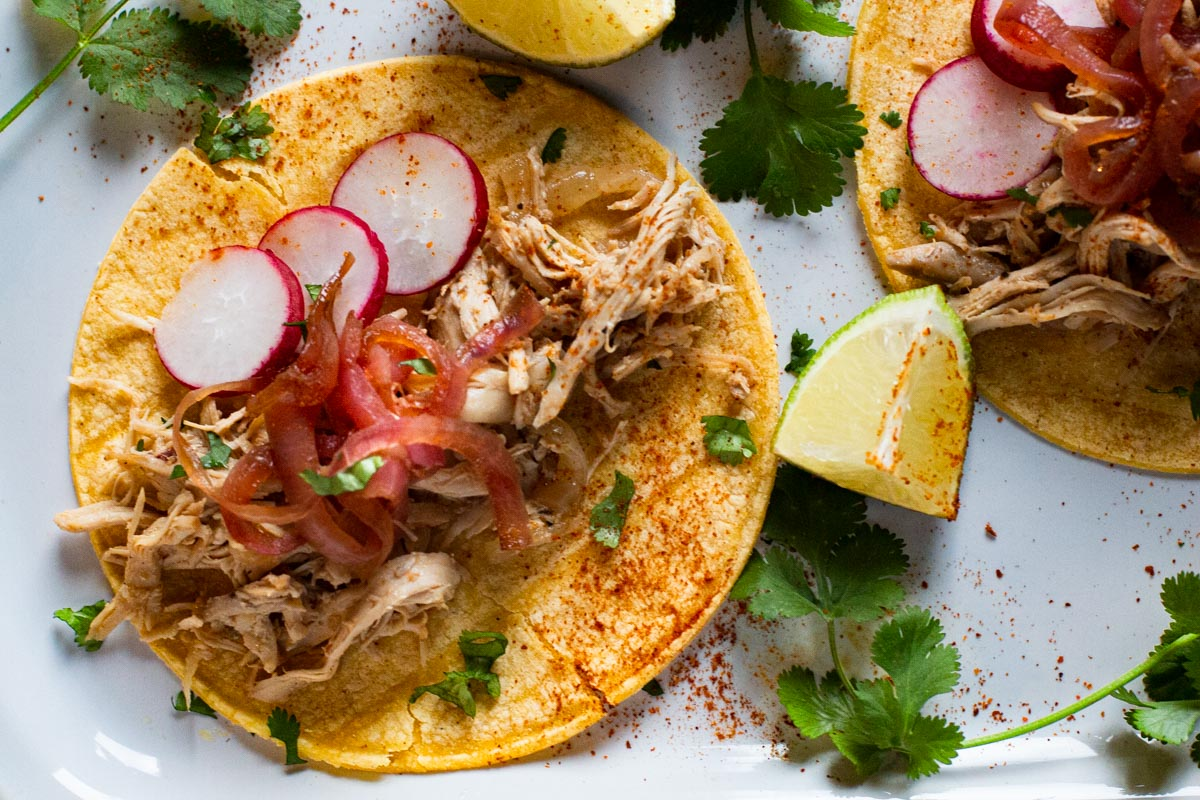 A recipe for Mexican barbacoa tacos using chicken topped with pickled onions and slices of radishes