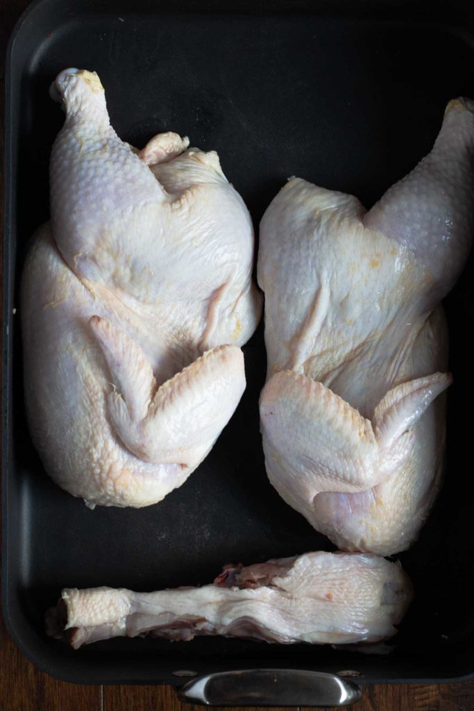 Cutting a chicken in half so it will lay flat to roast
