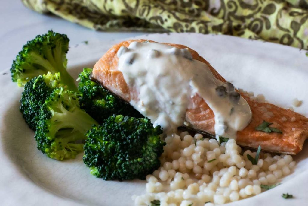 Roasted salmon topped with greek yogurt sauce served with broccoli and pearl couscous
