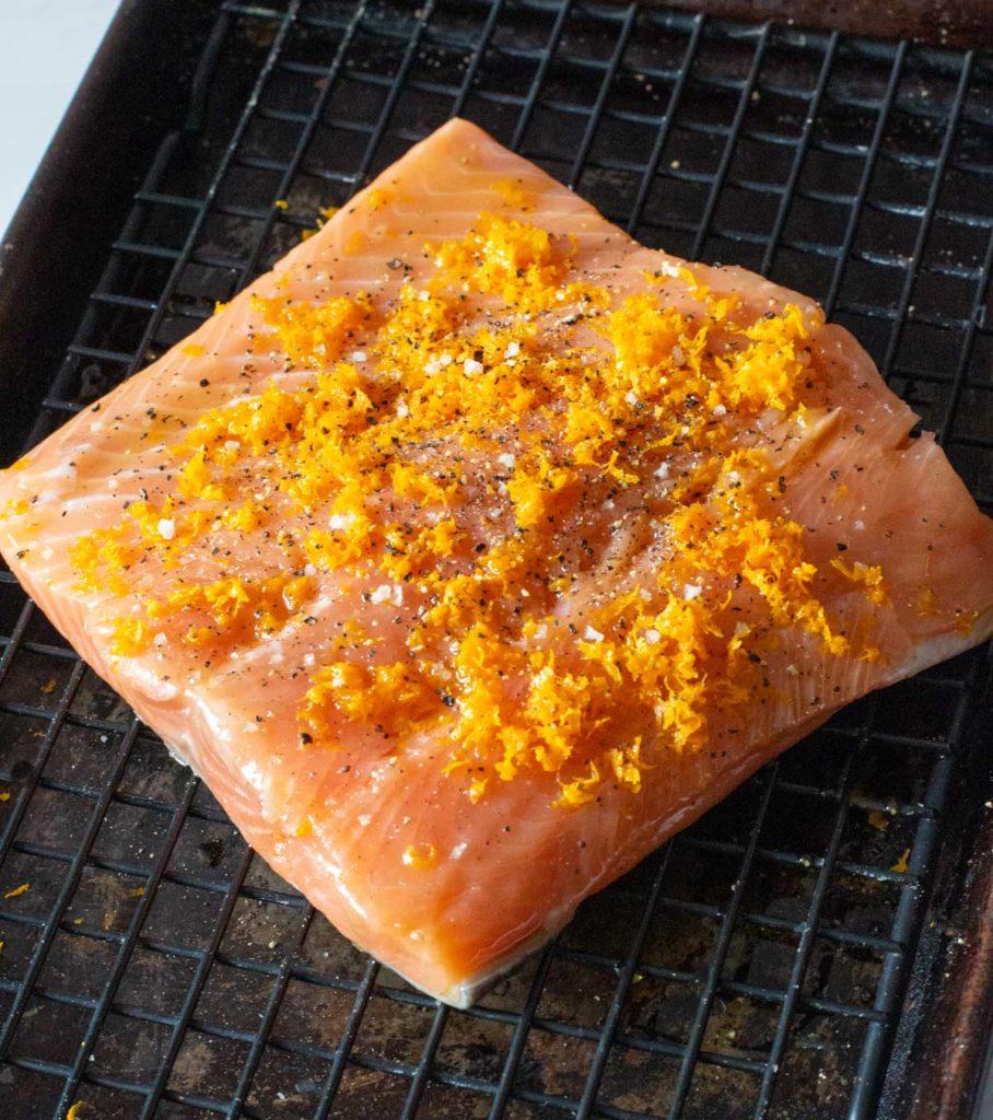 Salmon fillet sprinkled with orange zest salt and pepper to make orange salmon recipe