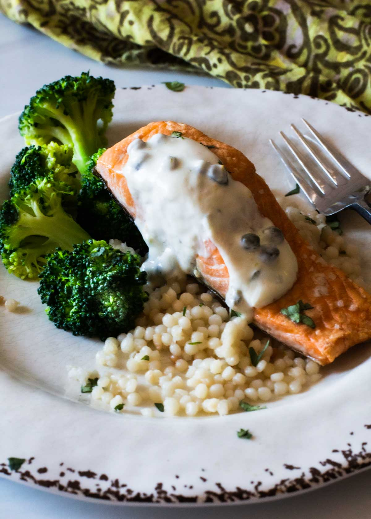 Salmon with yogurt sauce on a rustic plate served with broccoli and pearl couscous