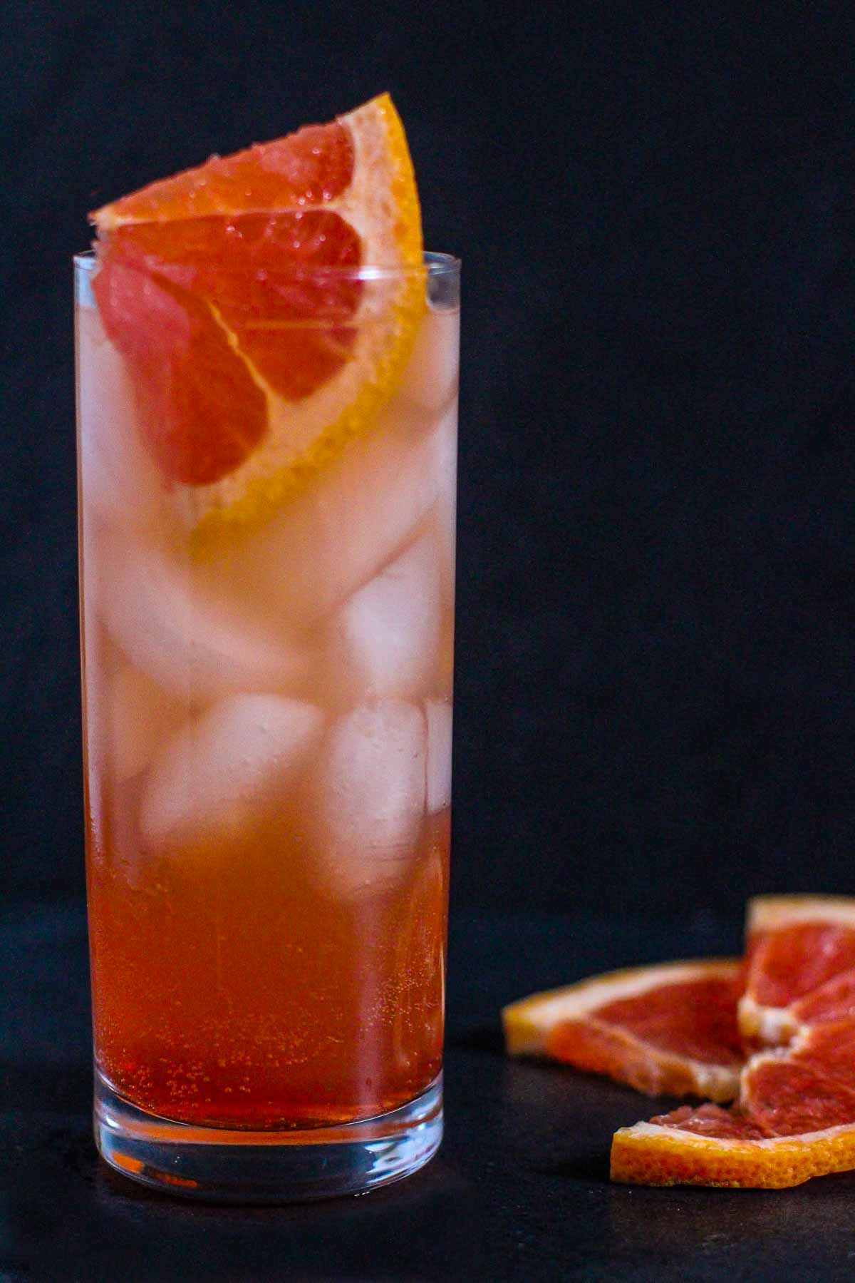 Paloma cocktail in a collins glass with slices of fresh grapefruit