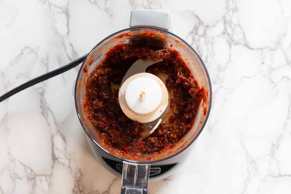 Using a small kitchen grinder processor to puree chipotle chile peppers in adobo sauce