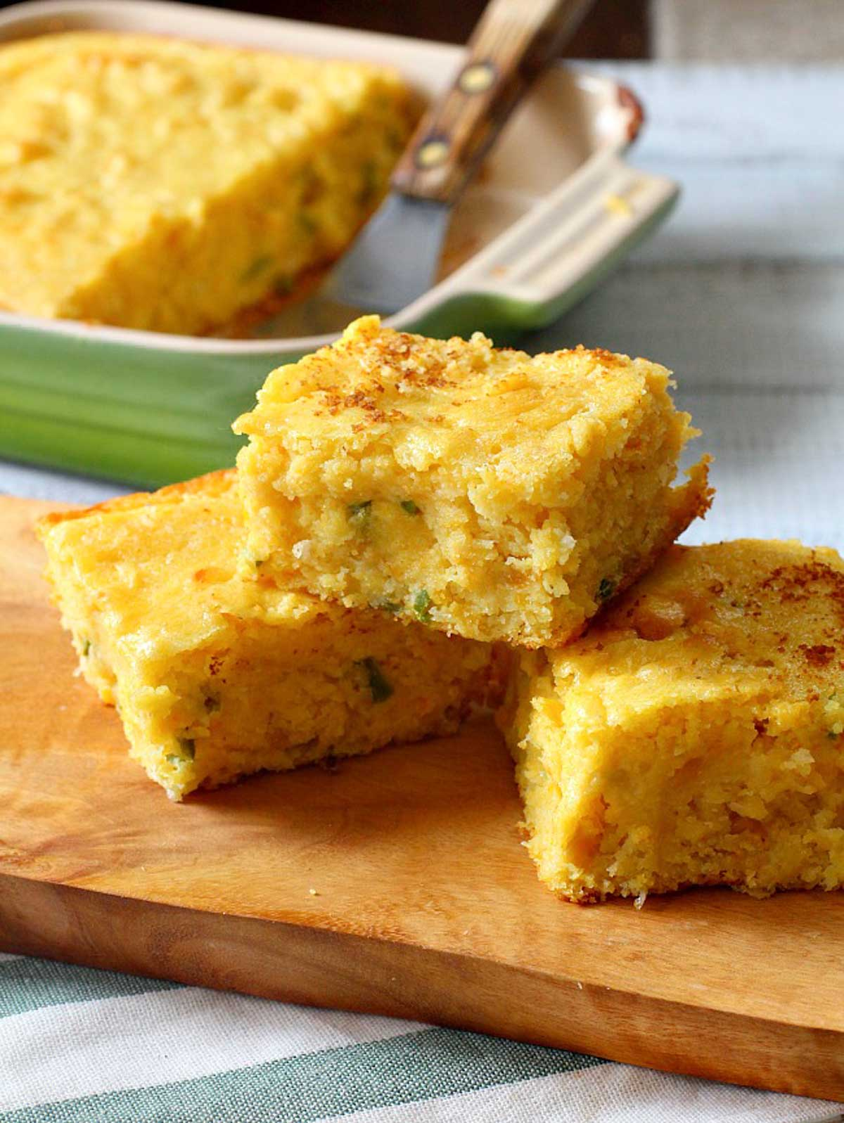 Super moist cornbread cut into squares on a wooden cutting board