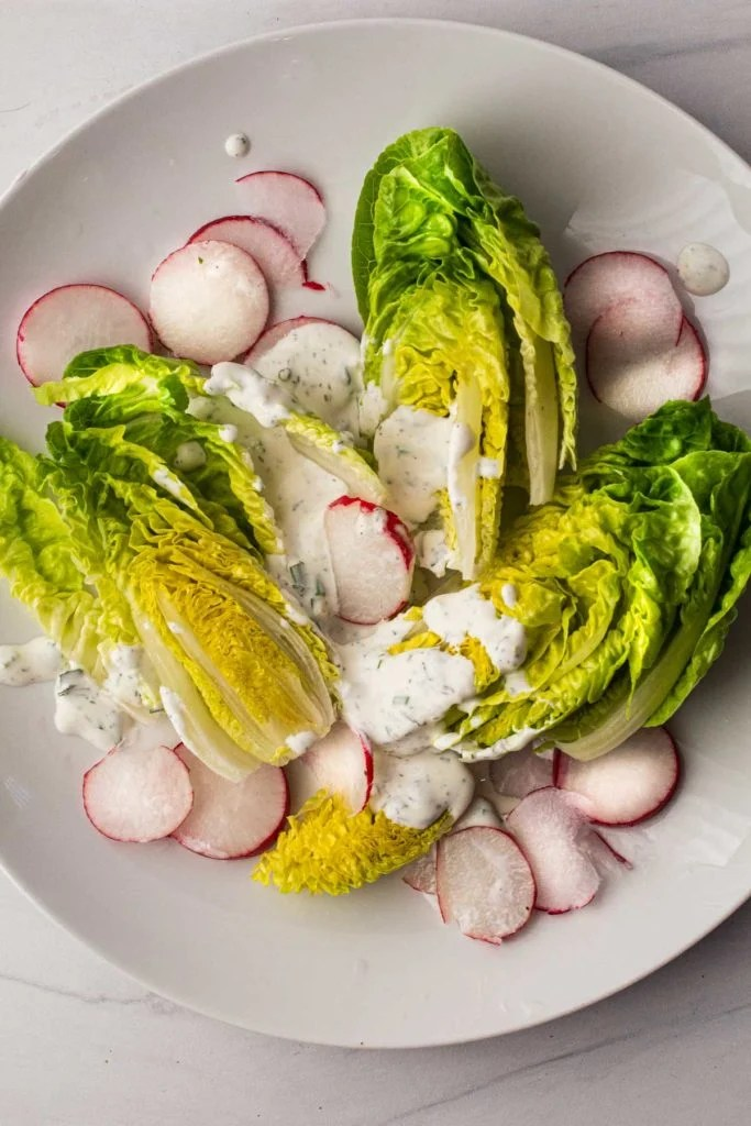 Homemade buttermilk ranch dressing on little gem salad with radishes