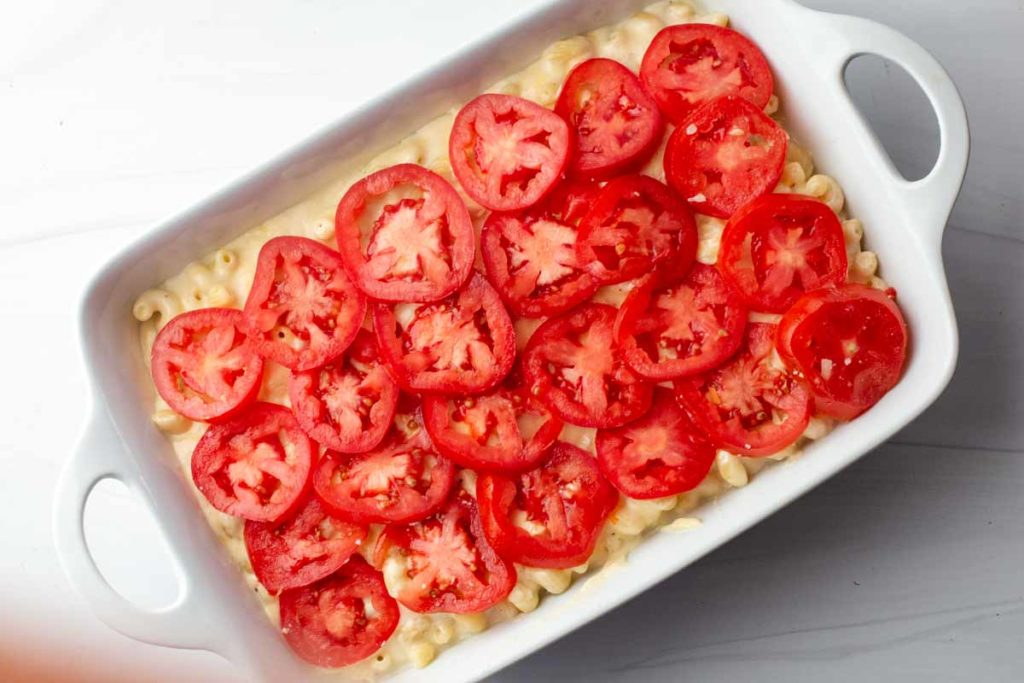 Sliced tomatoes on mac and cheese in a white casserole dish ready to bake