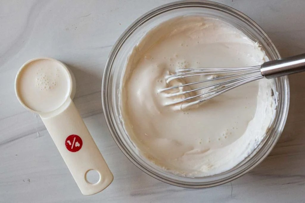 Whisking buttermilk in with mayonnaise and sour cream to make dressing