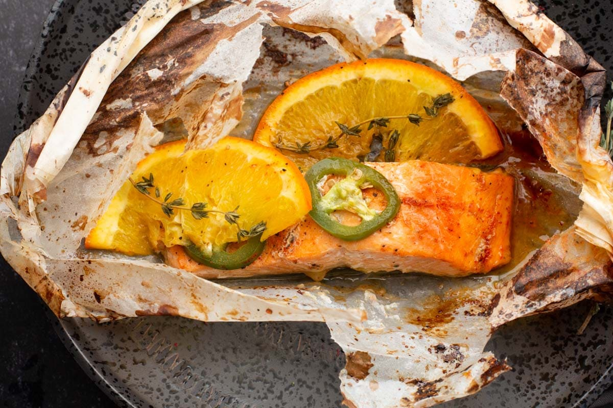 Salmon fillet cooked in parchment paper with oranges and jalapenos