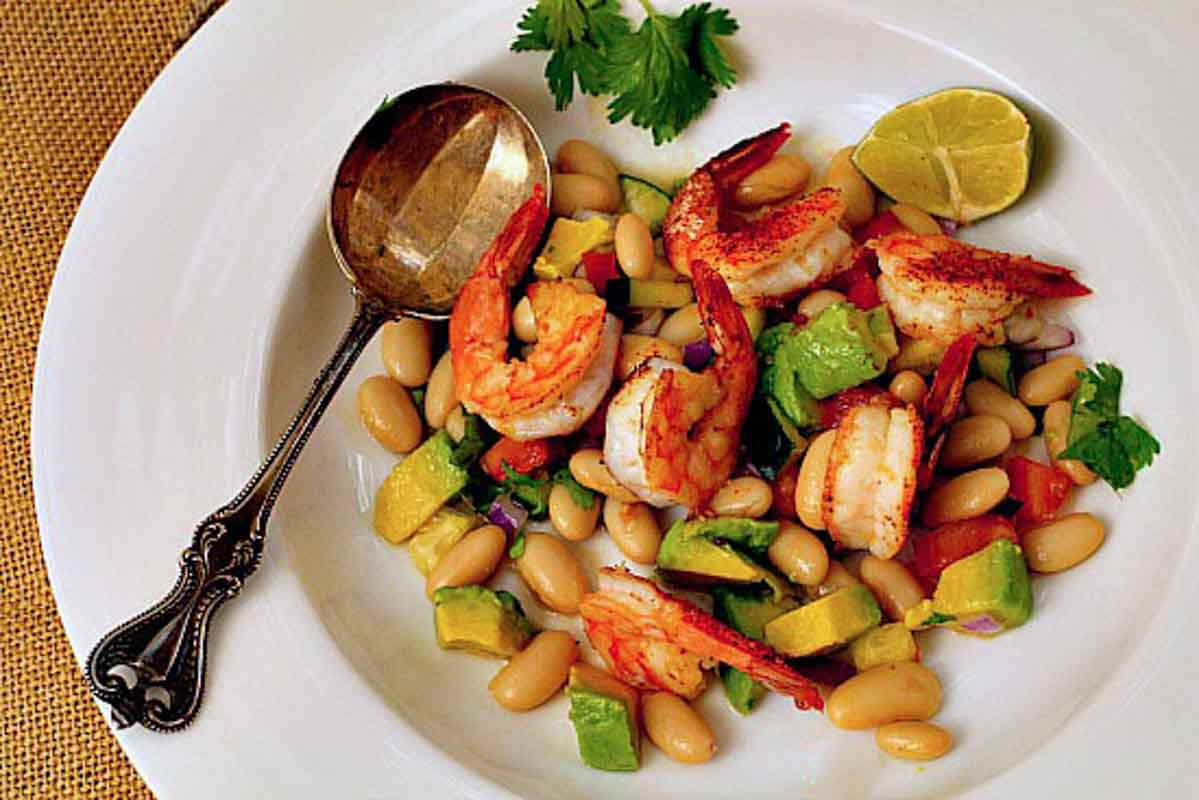 Roasted Shrimp Salad with avocado and canned white beans.Served with a wedge of lime in a white bowl
