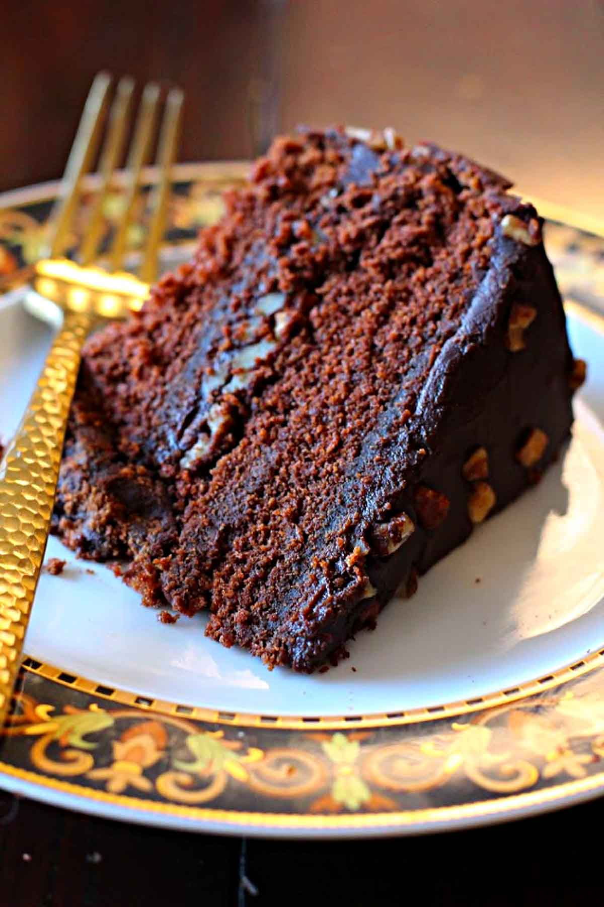 A slice of Chile chocolate cake with bourbon chocolate cake served on a Versace dessert plate with a gold flat ware fork