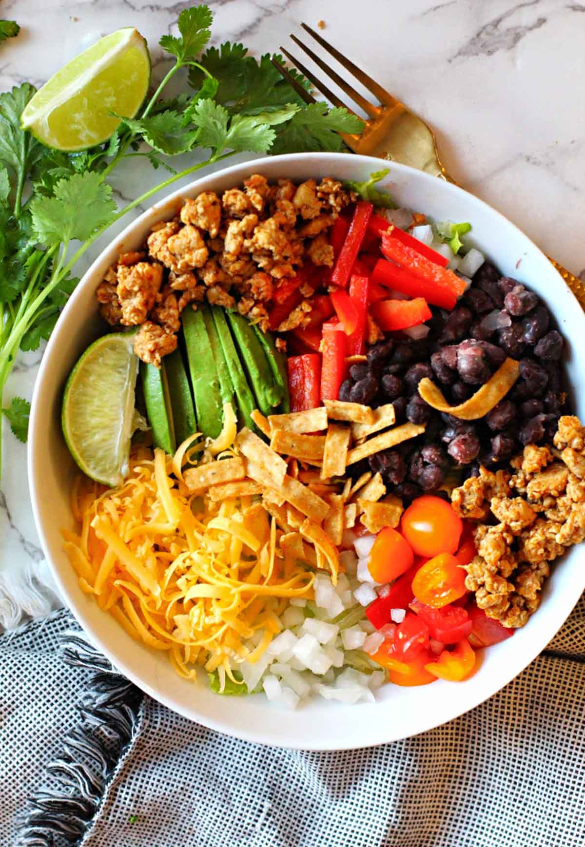 Chicken burrito bowl made with ground chicken breast served over rice and topped with cheese, black beans, avocado, red bell pepper, onions and cherry tomatoes.