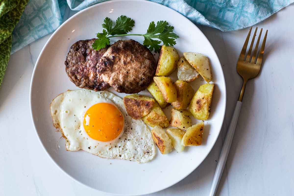 Ground turkey sausage patties with fried potatoes and a fried egg.