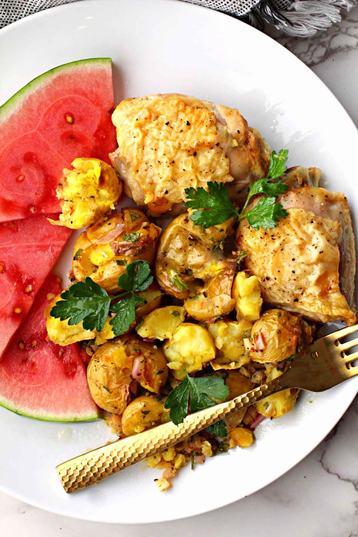lemon baked chicken thighs served with smashed potatoes and sliced watermelon