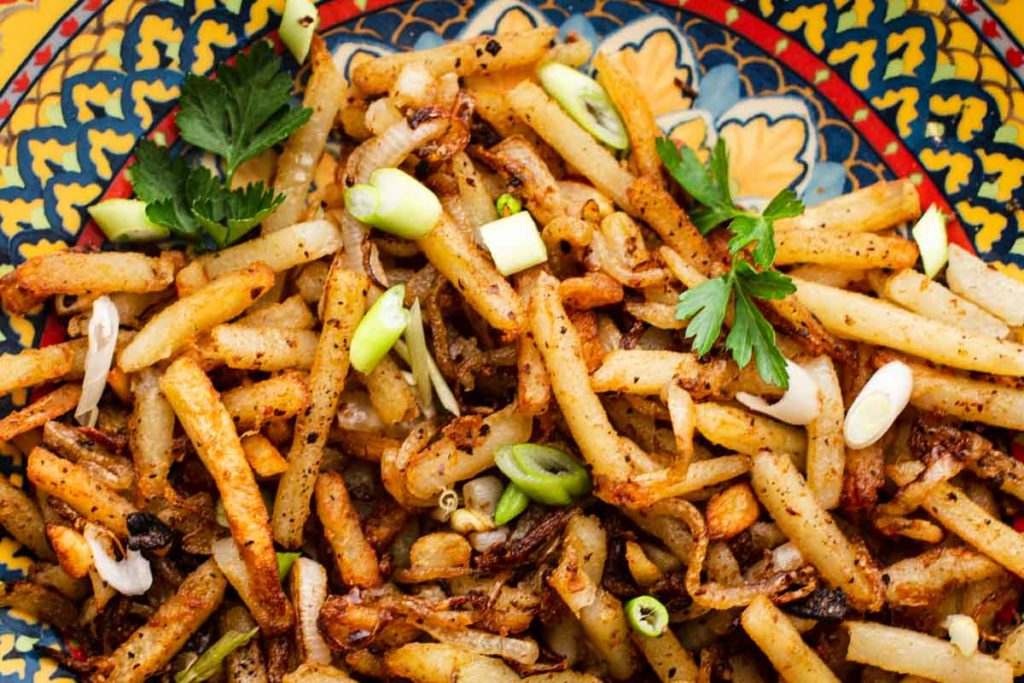 Turkish potatoes topped with green onions and garnished with parsley
