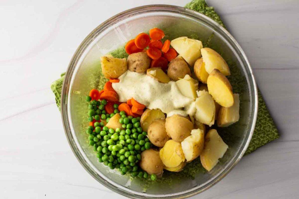 Mixing avocado cream sauce with potatoes, carrots and green peas to make avocado potato salad