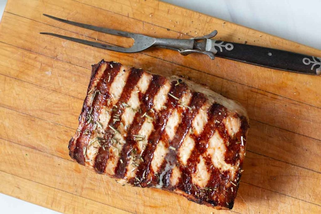 Grilled pork loin roast on a cutting board with an antique meat fork