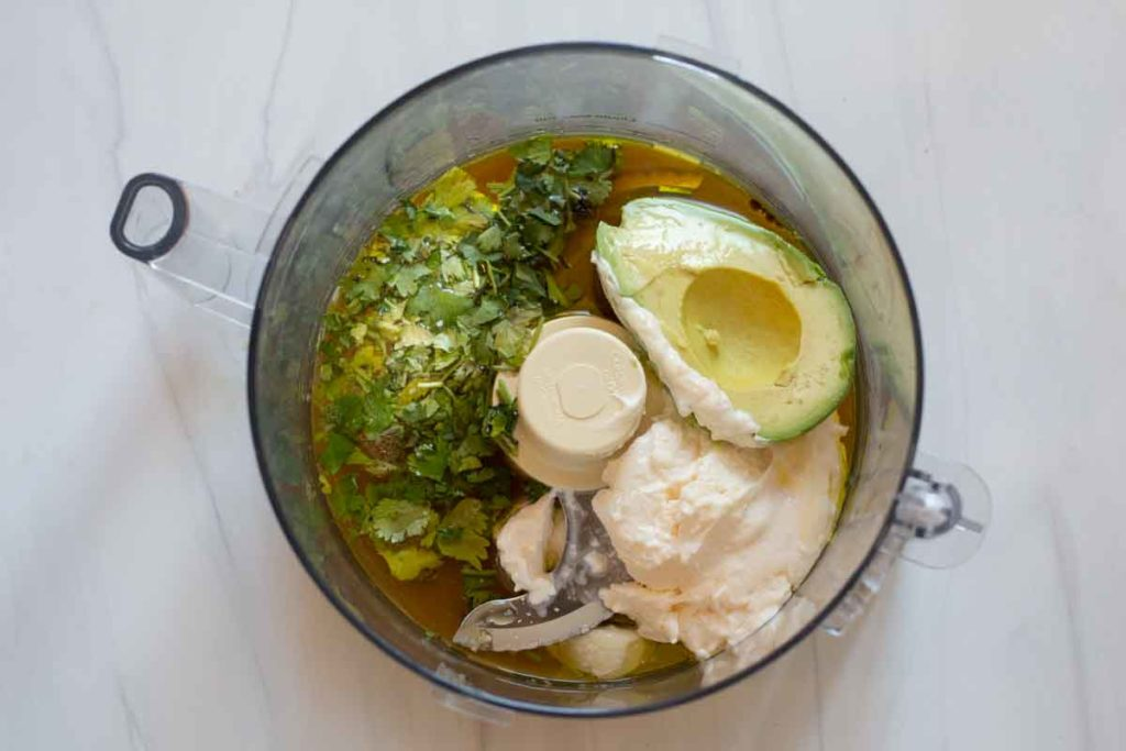 Using a food processor to blend avocado mayonnaise lime sauce