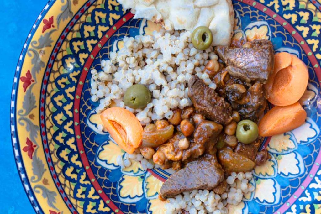 lamb tagine with apricots, chickpeas, and olives served over pearl couscous