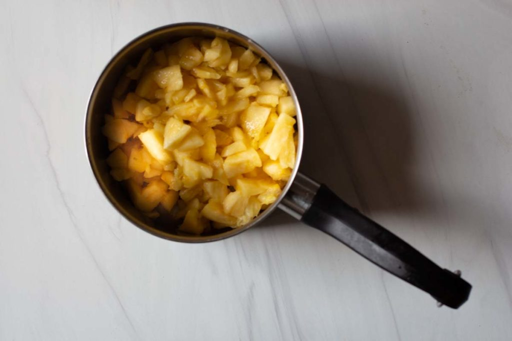 Cooking diced pineapple in a saucepan