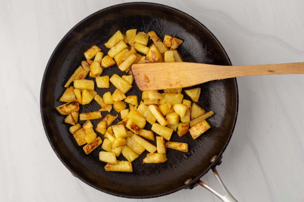 Frying pineapple pieces in a skillet
