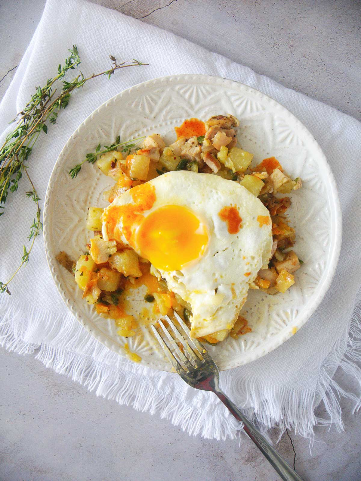 Chicken hash topped with a fried egg and a dash of hot sauce.