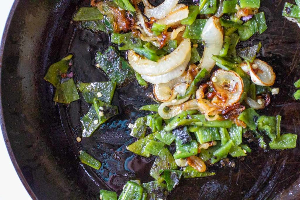 Roasted poblano peppers and caramelized onions in a fry pan